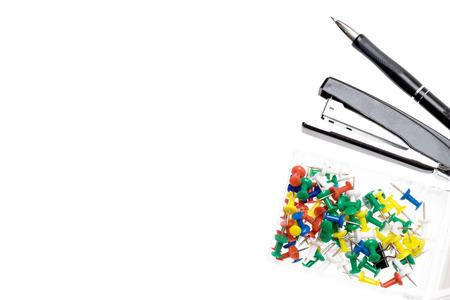 engrapadora: alfileres de colores, spapler y lápiz sobre fondo blanco. El espacio vacío para el texto. Fondo de la oficina concepto.