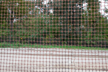 temporary: Temporary metal mesh along the road. Forest background