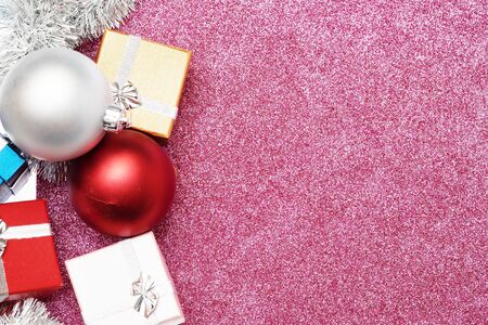 tinsel: Small boxes for gift and two christmas ball on red background, Empty space for text Stock Photo