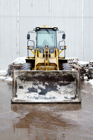 cargador frontal: One Loader excavator construction machinery equipment in an industrial zone. Front View.