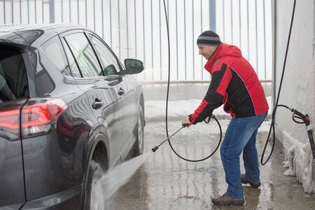 A man in red jacket washing his car in self-service station with high pressure blaster. Reklamní fotografie