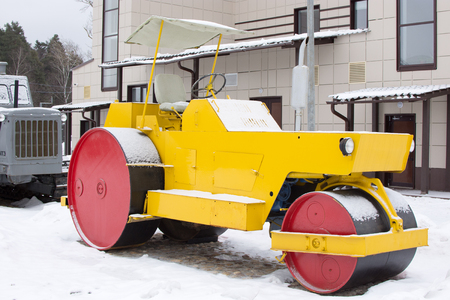 roller compactor: Yellow retro road roller at the winter landscape.