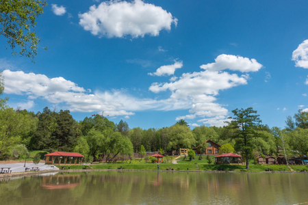Beautiful pond in the park. Blue sky with cloud and green forest. Summer landscape Stock Photo