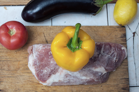 cutting: Frozen piece of meat on a wooden cutting board and yellow bell pepper, red tomato and eggplant on the table. Close up image