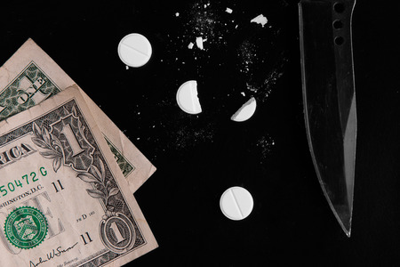 Drugs and money scattered on a black background Stock Photo