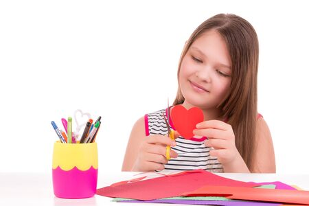Girl carves figures out of paper.Creative arts Stock Photo