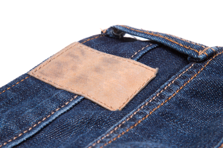 torn: Leather label on blue jeans. Blue denim fabric Stock Photo