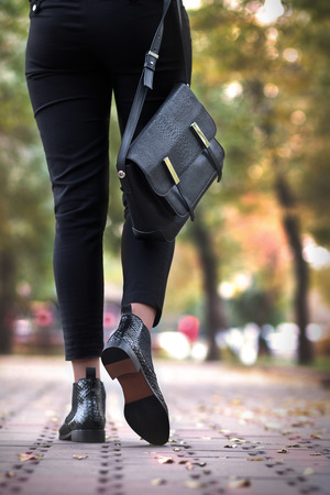 A girl steps in python leather shoes.