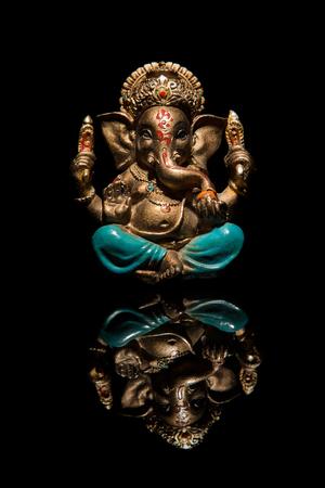 God of Ganesha with reflection on the surface. God of Ganesha with reflection on the surface. The deity of Ganesha on a black background