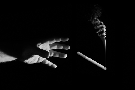 A mans hand reaches for a cigarette on a black background
