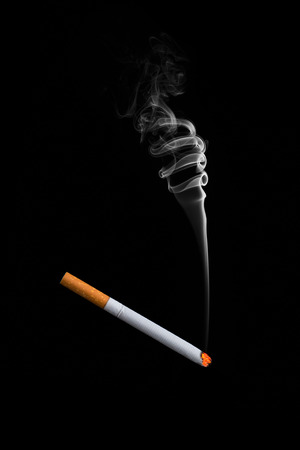 A cigarette stuck on a black background. Smoke from a fake cigarette.