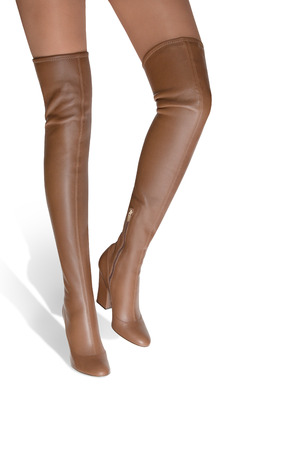 Hessian. A girl in high-heeled boots goes on an white background. Stock Photo