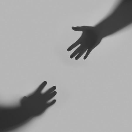 Two hands stretch towards each other against a gray background. Silhouettes of hands.