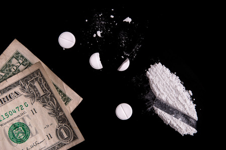 Drugs and money on a black background