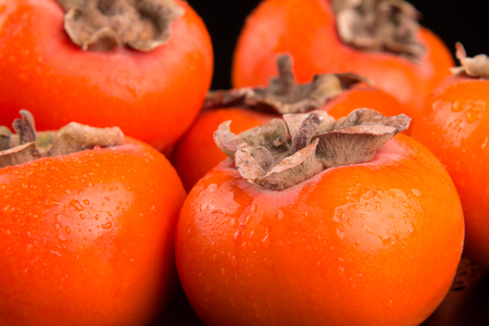 Fruits of fresh persimmons on a black background
