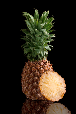 Fresh pineapple with a cut piece on a black background Stock Photo
