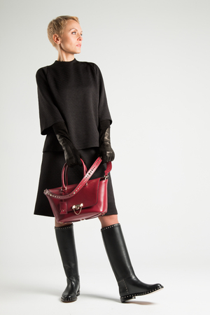 A girl in boots with thorns and a red stylish bag