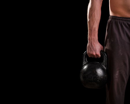 Kettlebell in the hand on a black background Stock Photo