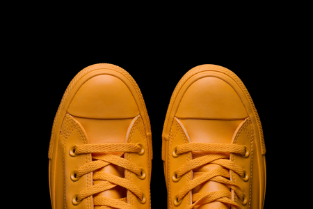 Stylish sneakers yellow on a black background. Yellow sneakers.