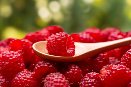 Fresh raspberries and a wooden spoon