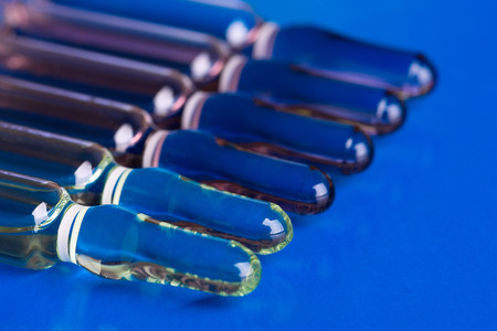 Medical ampoules lying in a row on a blue background