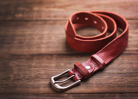 Girdle of red leather. Fashionable leather belt on a wooden table.