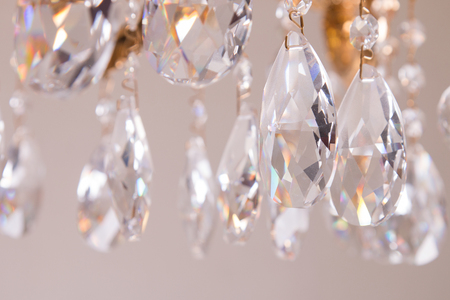 Gallant chandelier with light candles. Luxury candelabra hanging on ceiling with lots of little gems. Stockfoto