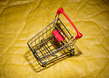Trolley under the products standing on a yellow paper background. Abstraction.