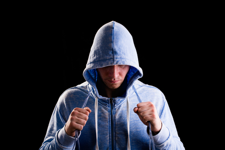 Athlete in hood on a black background. Drops of sweat from training.