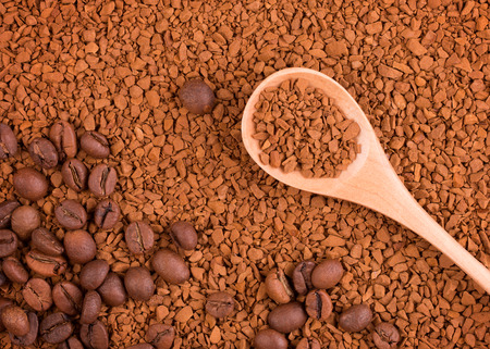 Instant coffee in a wooden spoon. Two states of coffee beans and soluble granules.