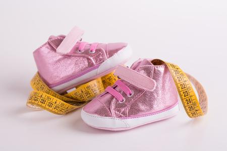 Zapatos de niños. Crecimiento del pie del bebé. Cinta amarilla dimensional y zapatos de bebé.