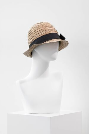 White faceless mannequin in a straw hat. Mannequin in the store.