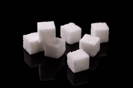 Cubes of sugar. Refined sugar on the black mirror surface of the table.