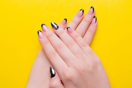 Girls hands with a manicure on a yellow background.