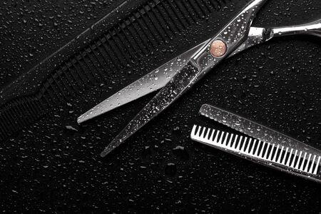 Scissors and a hairdresser comb closeup on a black background. Stok Fotoğraf