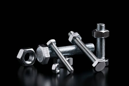 Still life with steel bolts and nuts on a black background.