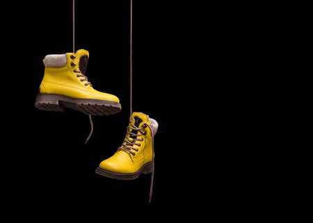 A pair of yellow shoes hanging on a cord. Yellow shoes on a black background. Stok Fotoğraf - 128350158