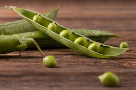 Green peas on wooden background.