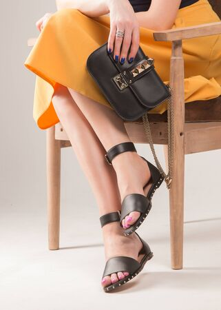 Girl with a fashionable handbag on the chair. Girl in sandals. Stok Fotoğraf