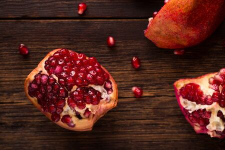 Fruits of ripe pomegranate on wooden background.