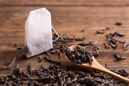 Tea bag and tea leaves with a spoon on a wooden background.