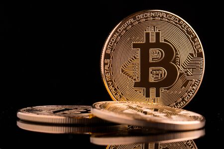 Bitcoin gold coins on a black background.