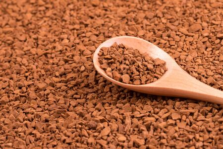 Instant granulated coffee and wooden spoon.