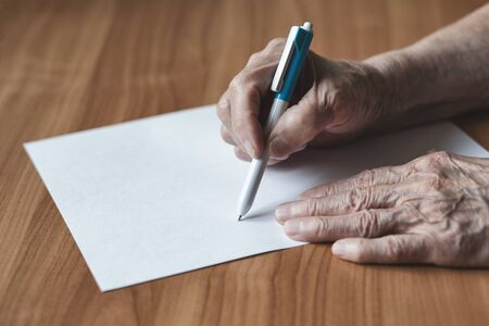 Old woman pensioner writes on a piece of paper.