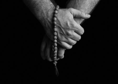 Church rosaries in the hands of men on a black background. Stock Photo
