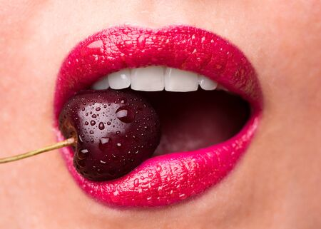 The girl bites a ripe cherry. Cherry in mouth close up. Stok Fotoğraf