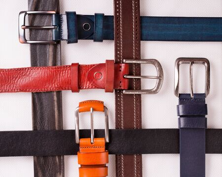 Colored leather belts on a white background. Stok Fotoğraf