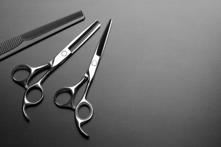 Barber scissors and comb on a dark background.