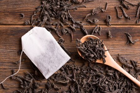 Loose tea in a spoon and tea bag on a wooden background.