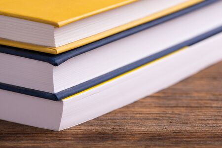 Books close up. A stack of books lying on a wooden table. Stok Fotoğraf - 128345924